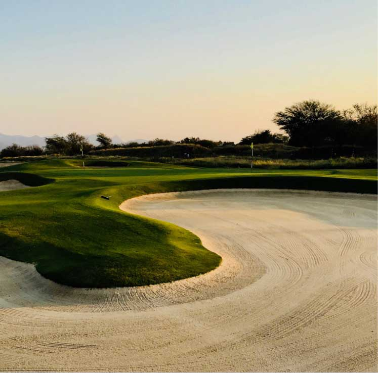 Sand trap near hole on golf course