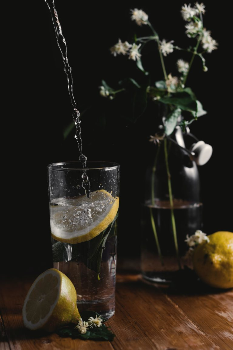 Glass of Gin and tonic with swizzle stick and lemons on a wooden table