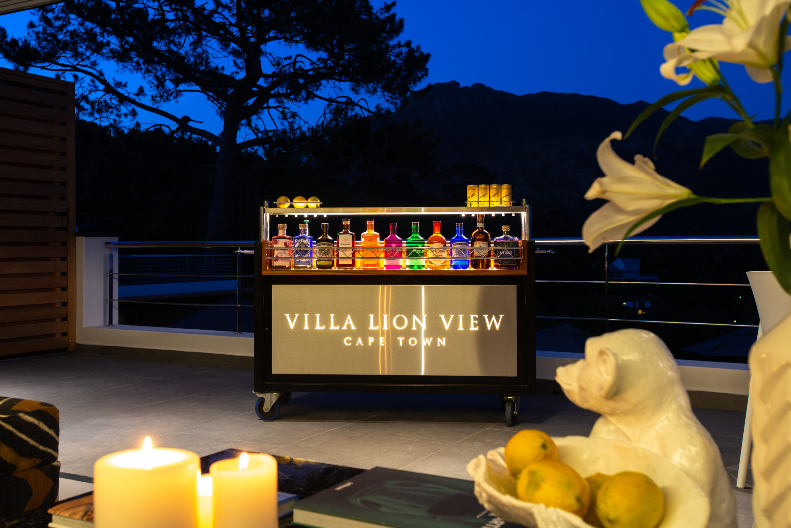 Bar with alcohol in the evening outside with candles at Villa Lion View