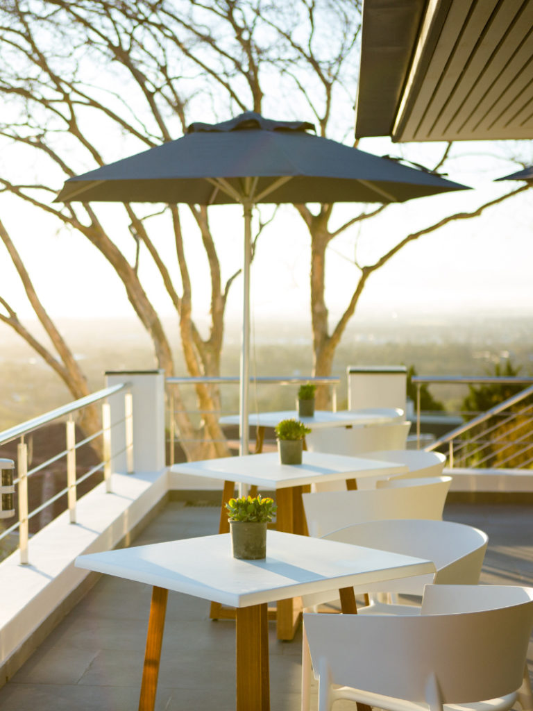 Outdoor seating area with tables, chairs and umbrella at Villa Lion View