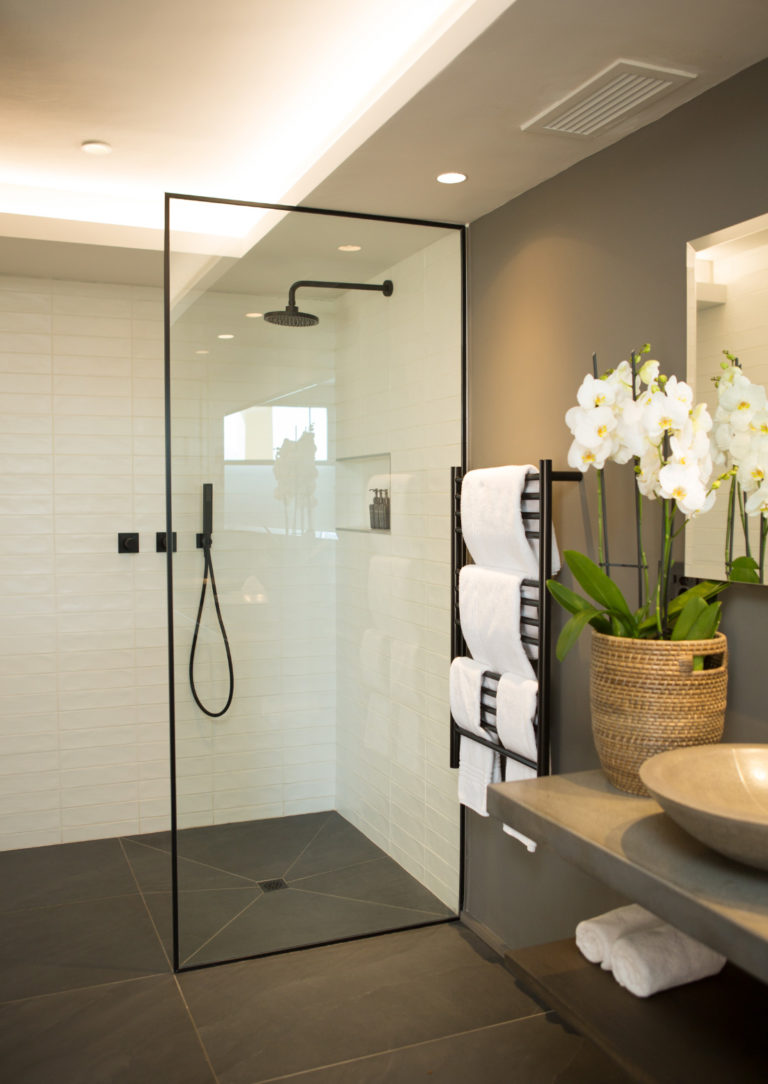 En-suite bathroom with walk in shower with fresh towels and flowers in Deluxe Room at Villa Lion View