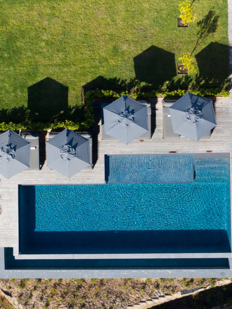 Infinity pool with sun loungers with umbrellas and grass at Villa Lion View