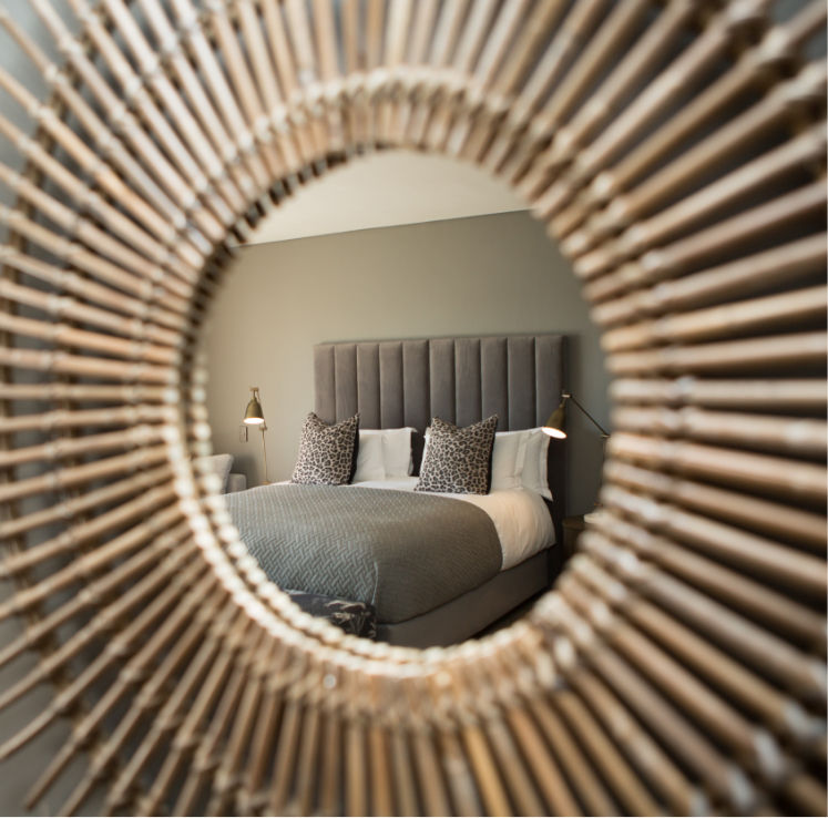 View of bed in mirror in luxury bedroom at Villa Lion View